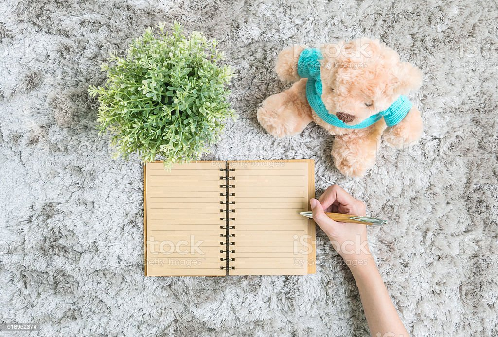 woman lied on gray carpet writing at a note book stock photo