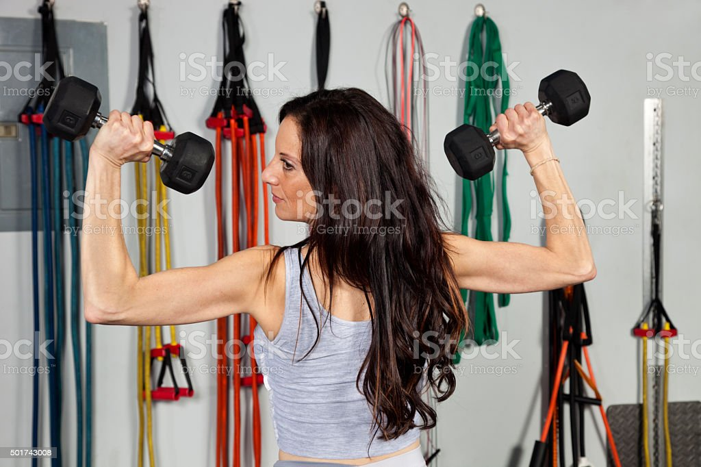 Woman lifting dumbbells over head in a press exercise stock photo