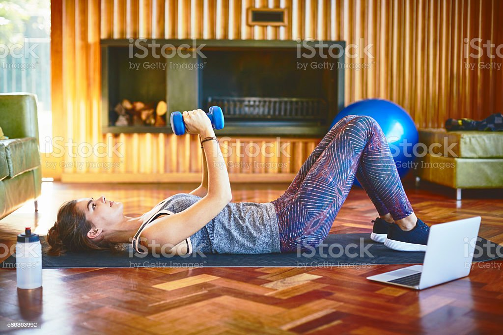 Woman lifting dumbbells while lying on floor at home stock photo