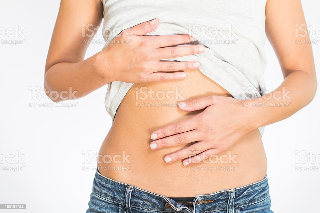 Woman lifting shirt and touching stomach stock photo