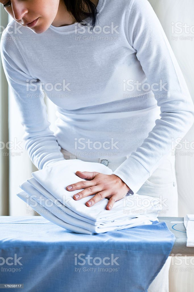 Woman Lifting Up Pile Of Ironed Folded Shirts royalty-free stock photo