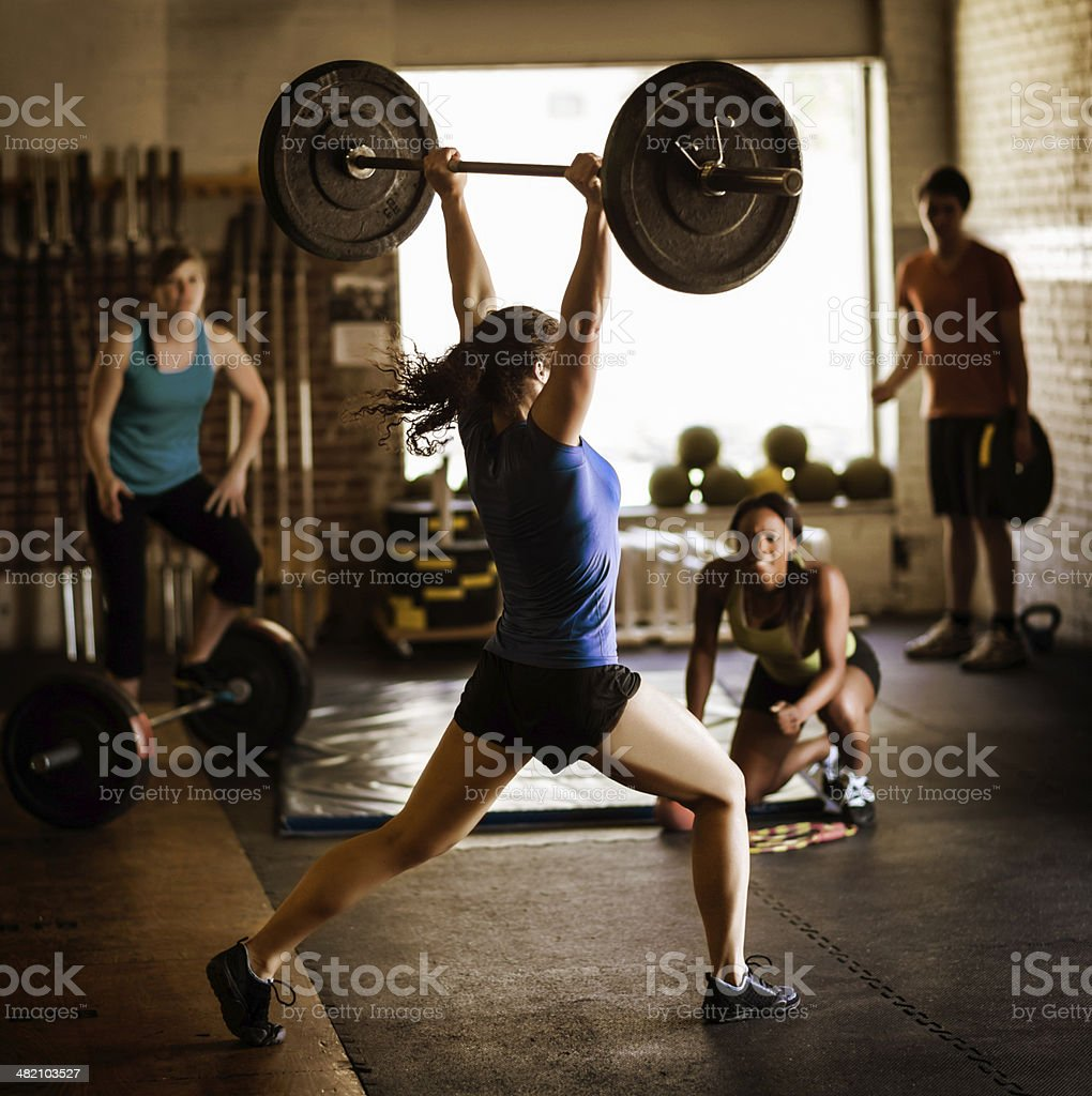 Woman Lifting Weight In Gym stock photo