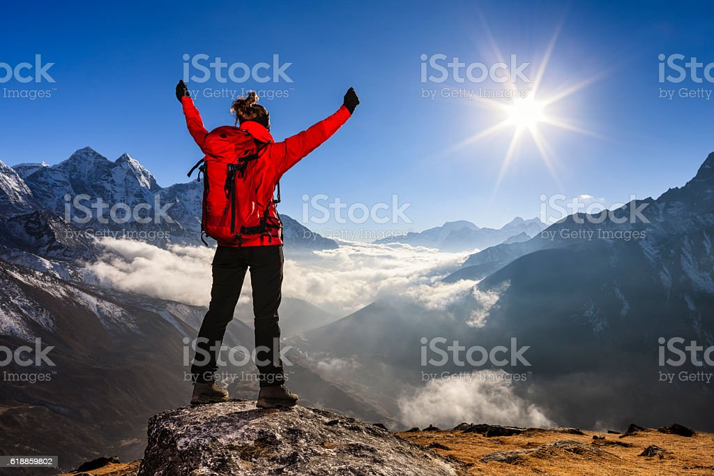 Woman lifts her arms in victory, Mount Everest National Park stock photo