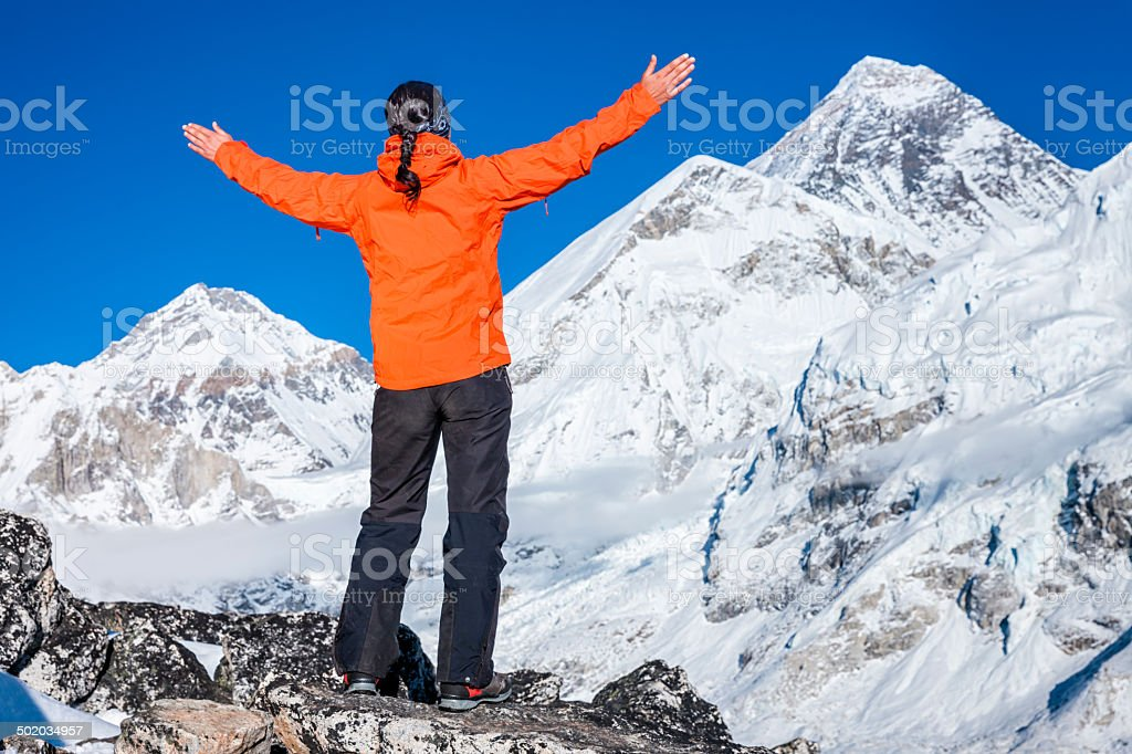 Woman lifts her arms in victory, Mount Everest on background stock photo