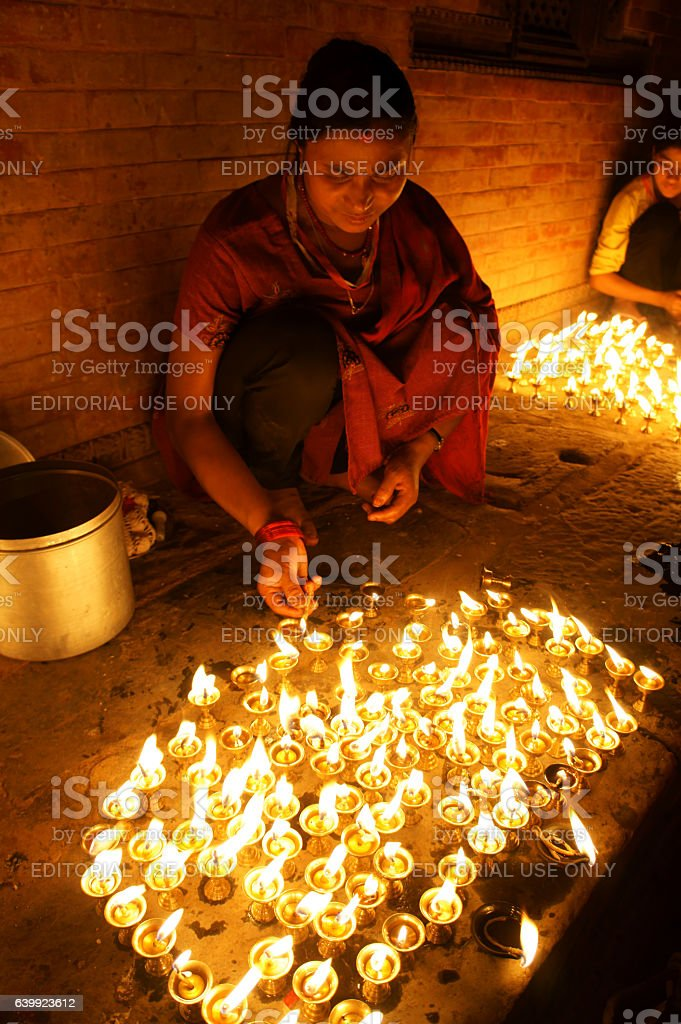 woman lighting candle lights in the night stock photo
