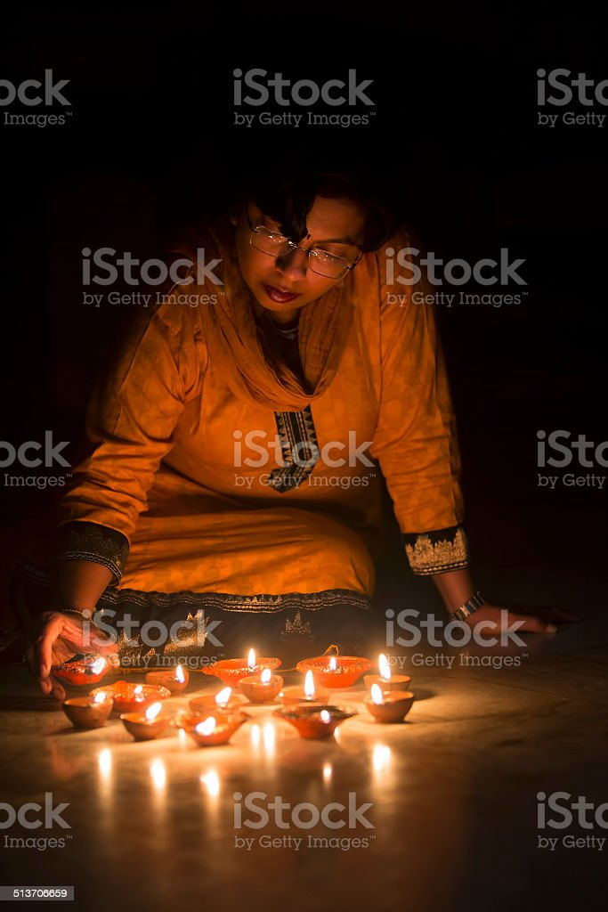 Woman lighting diyas or Oil lamps for Diwali stock photo