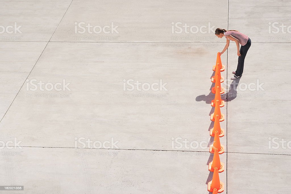 Woman lining up traffic cones stock photo