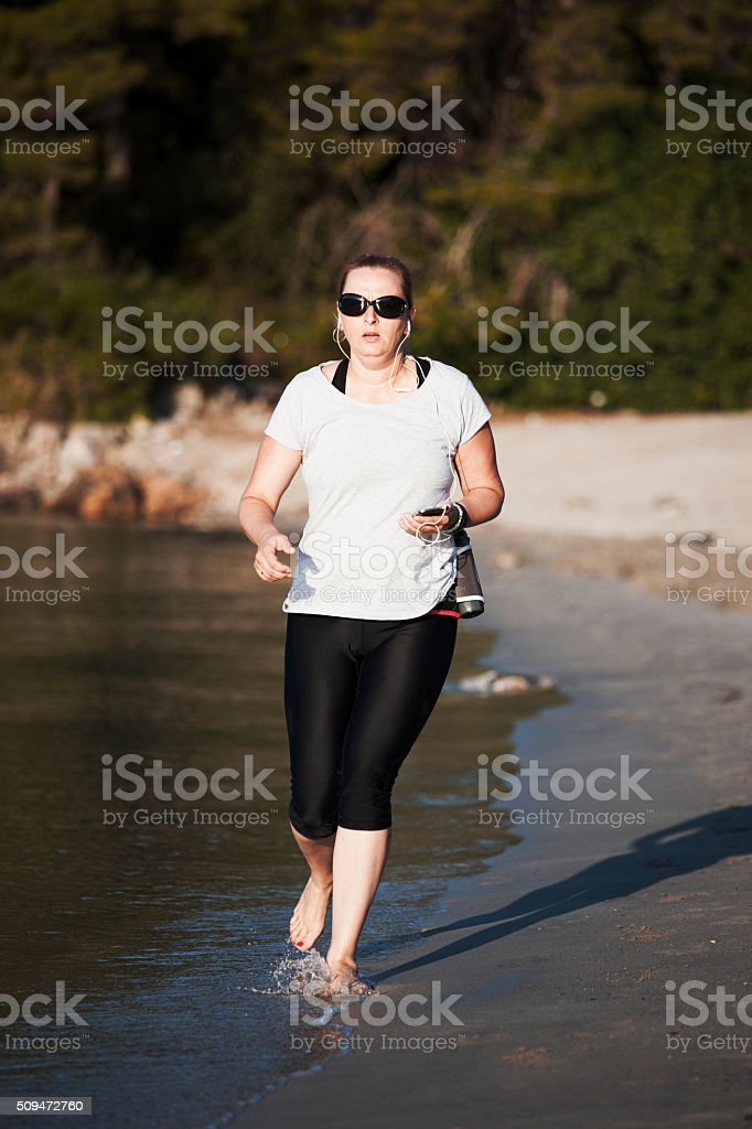 Woman listen music and jogging on the beach stock photo