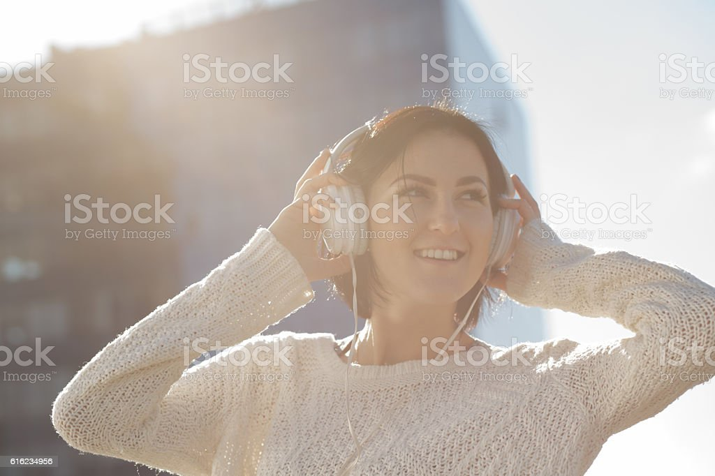 Woman listen music at building background, low contrast image stock photo