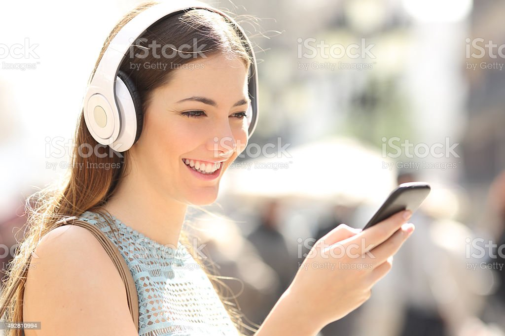 Woman listening music from a smart phone in the street stock photo
