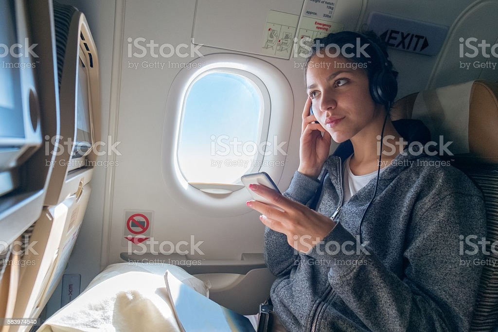 Woman listening music in airplane stock photo
