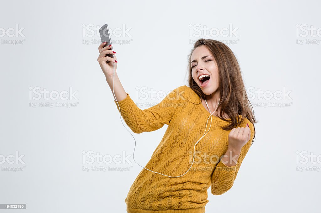 Woman listening music in headphones and dancing stock photo