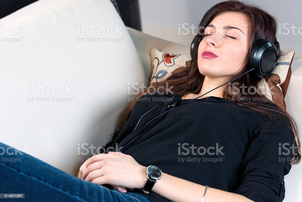 Woman listening music on the sofa stock photo