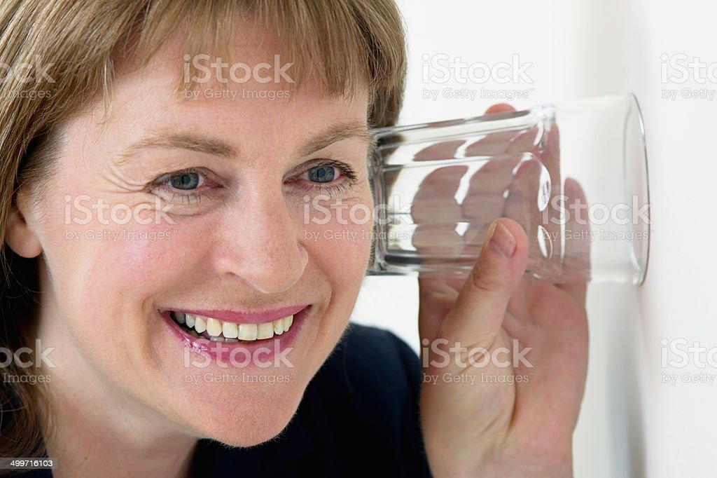 Femme écoute au mur avec une oreille un verre photo libre de droits