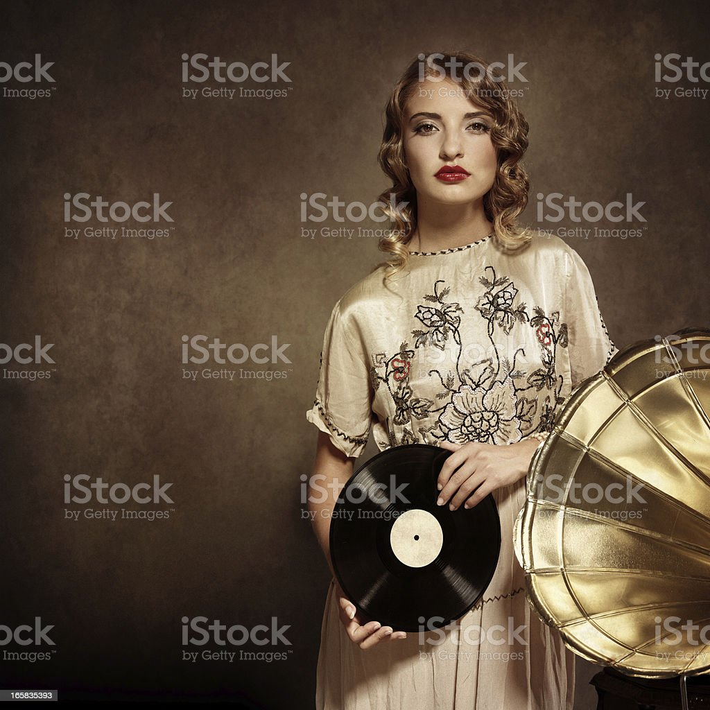 woman listening to music and holding an old vinil record stock photo