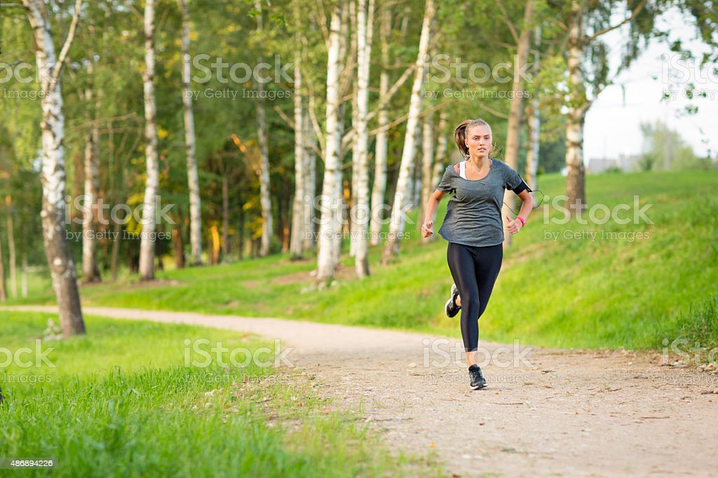 Woman listening to music and running in Dusk stock photo