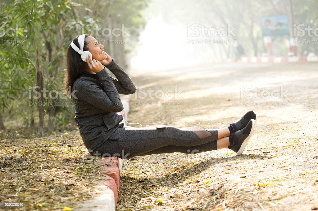 Woman listening to music on smart phone stock photo
