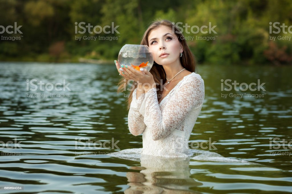 Woman listens to a goldfish. stock photo