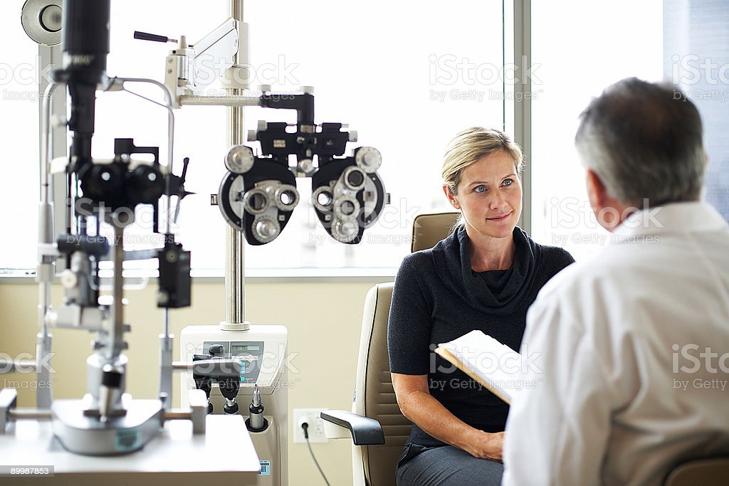 A woman listens to her opthamologist stock photo