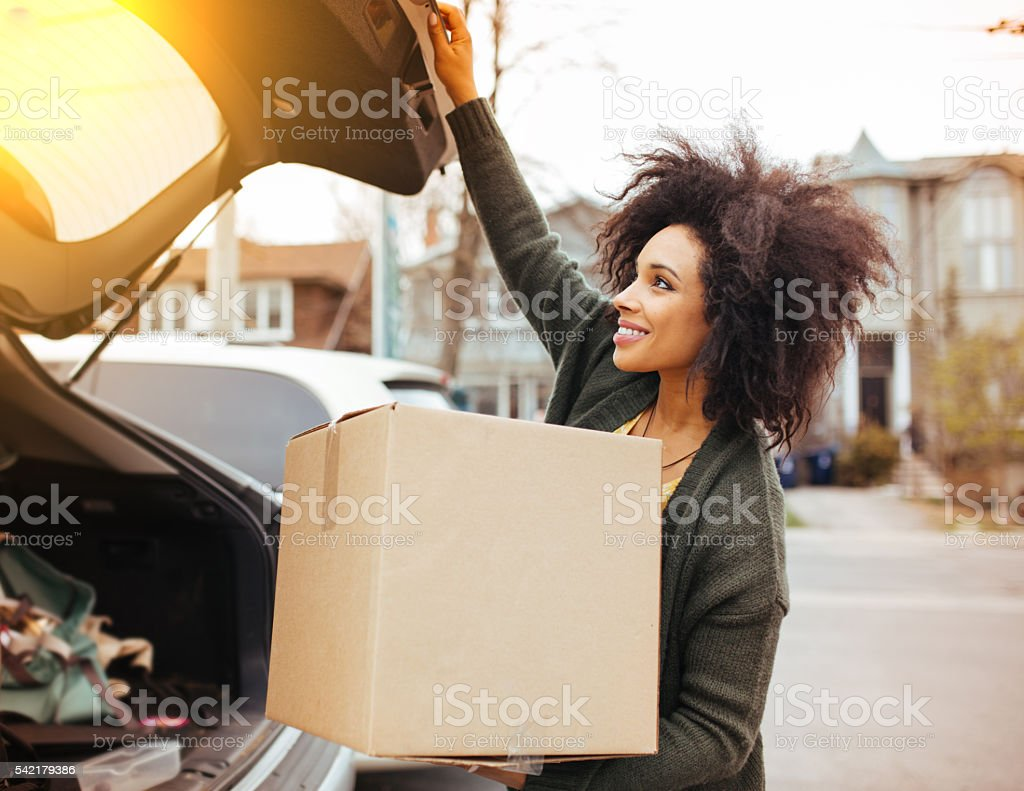 Woman load the car with moving boxes stock photo