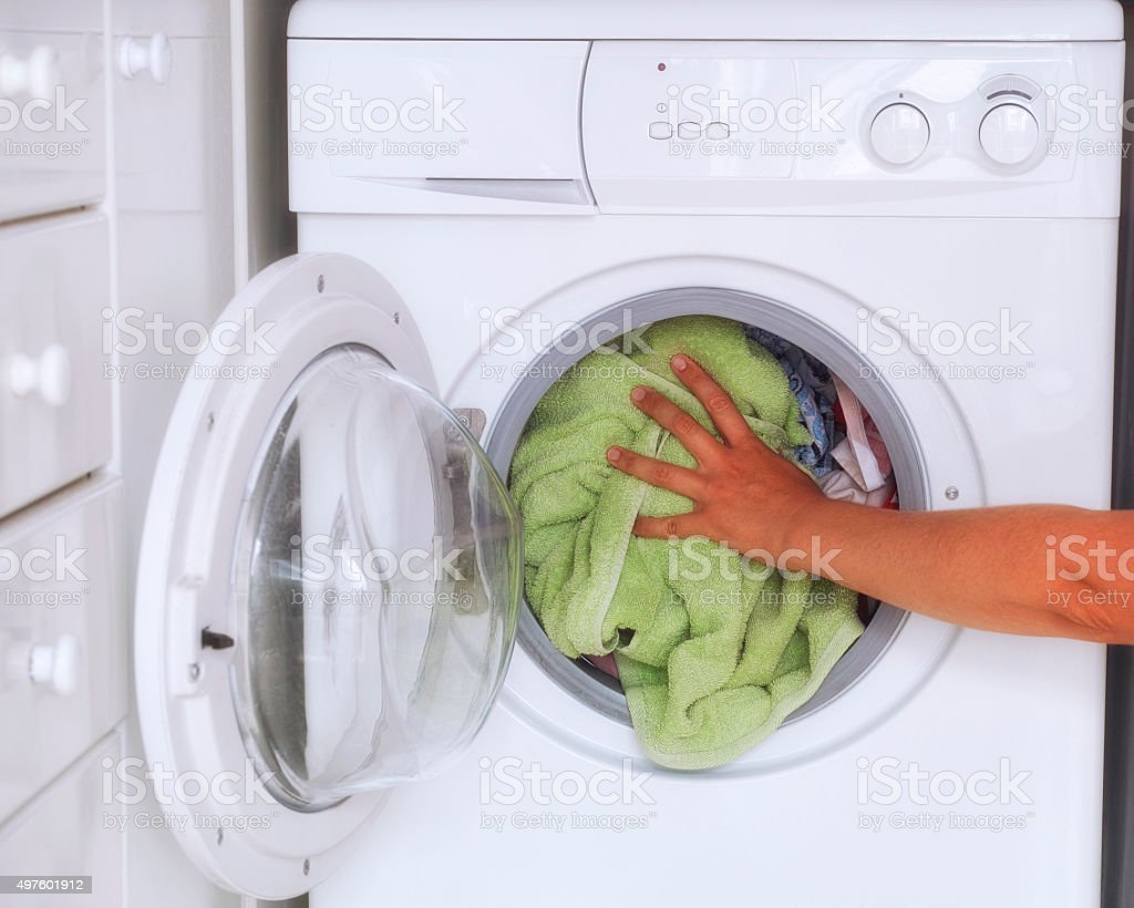 Woman loaded clothes into washing machine stock photo