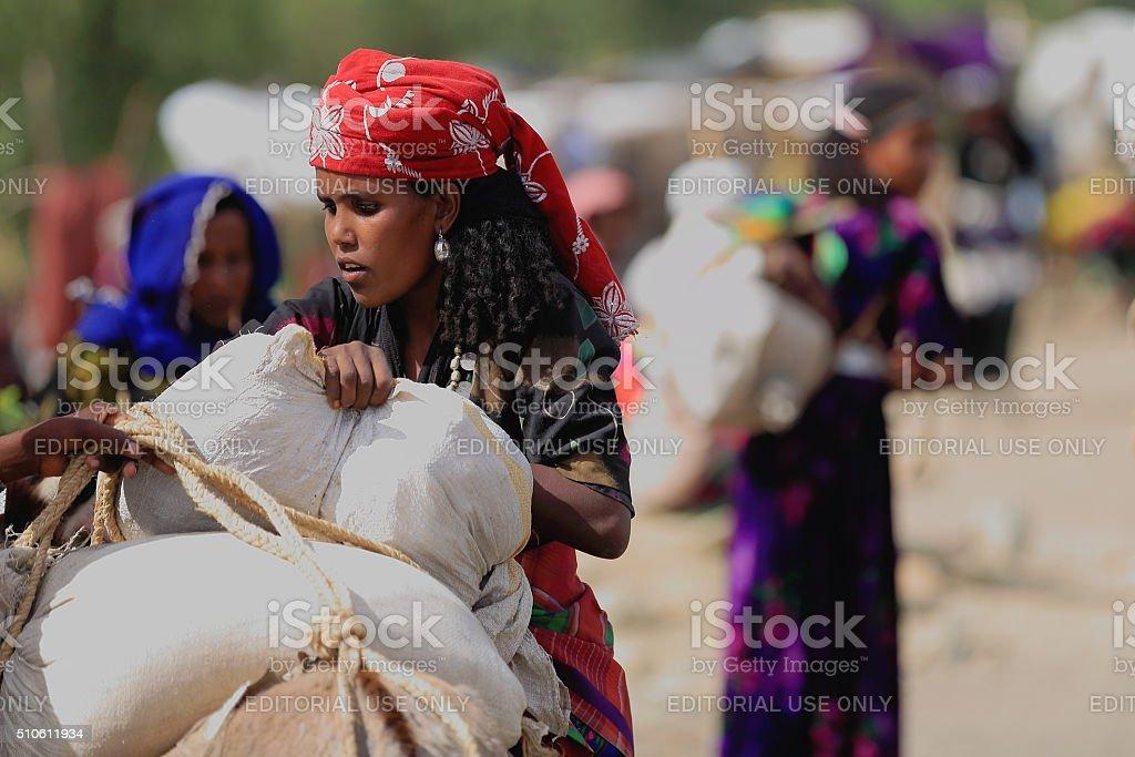 Woman loading sacks on a dromedary. Senbete-Ethiopia. 0067 stock photo