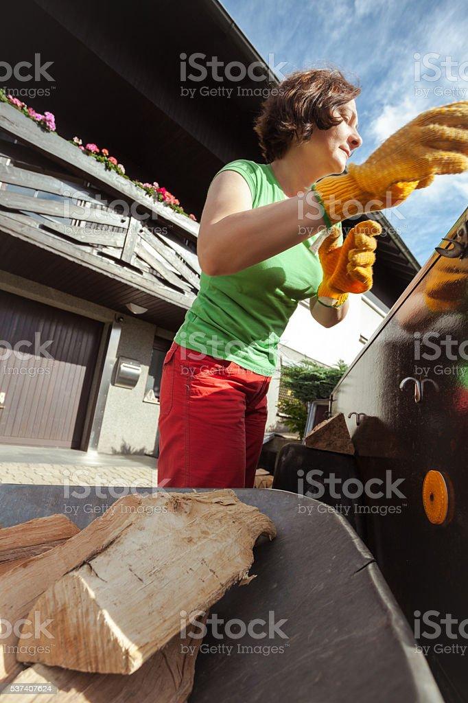 Woman loading wheelbarrow with firewood stock photo