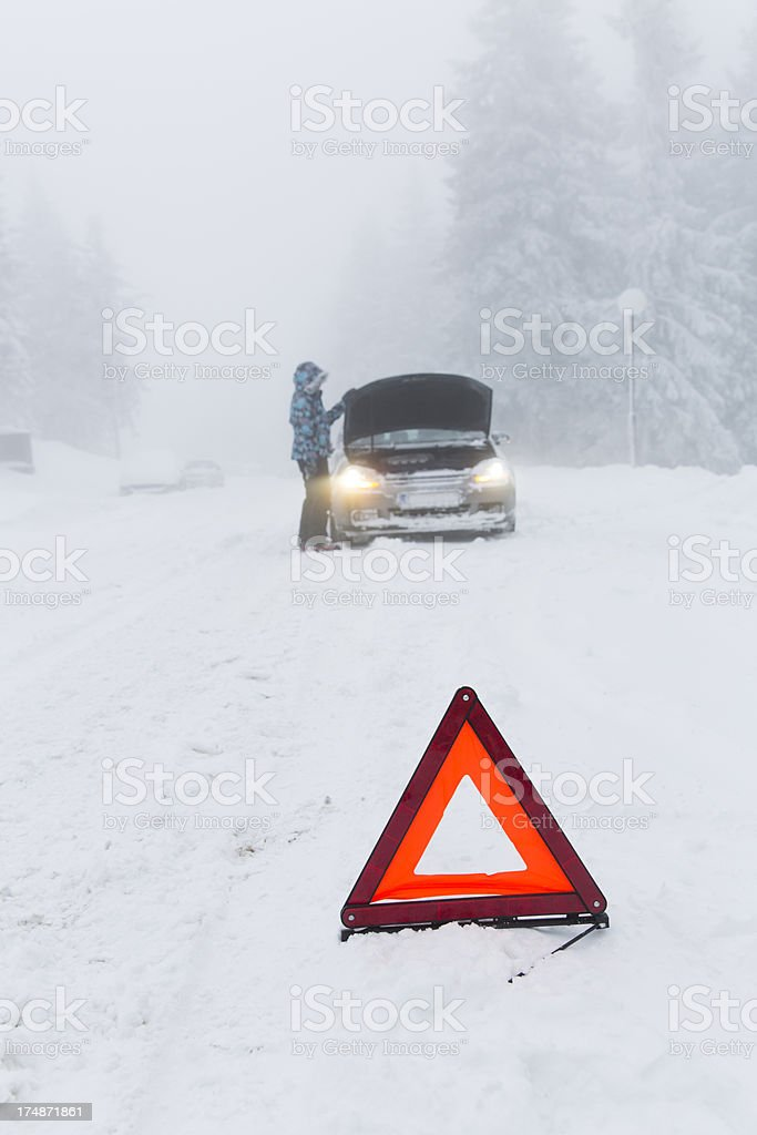 Woman loking at her broken car in snow blizzard...warning triangle royalty-free stock photo
