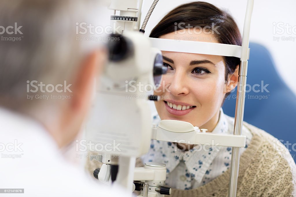 Woman look in ophthalmoscope stock photo