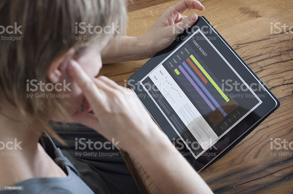 Woman Looking a Family Report on Tablet stock photo