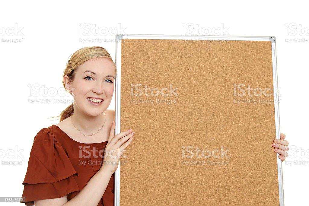 Woman looking at a blank noticebaord stock photo