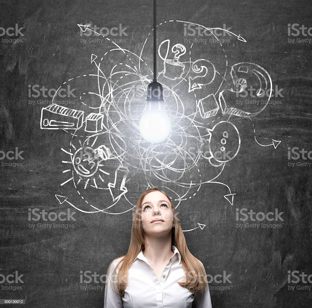 woman looking at a bulb thinking about problem solution stock photo