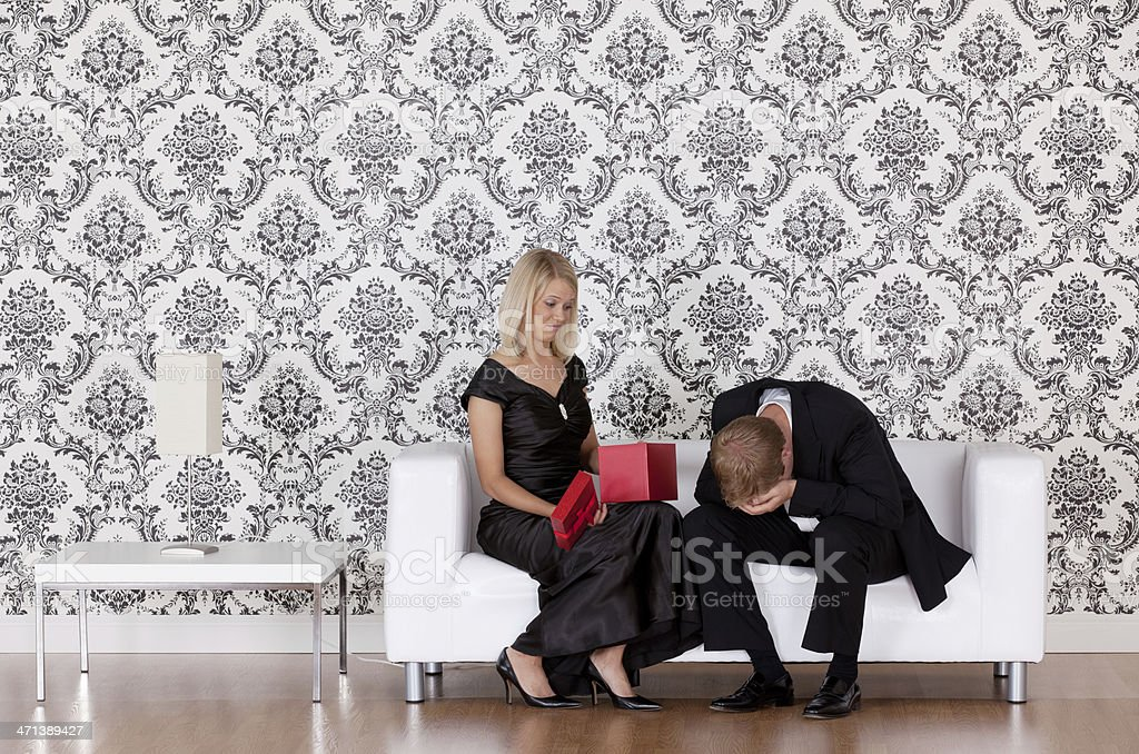 Woman looking at a gift given by her husband royalty-free stock photo