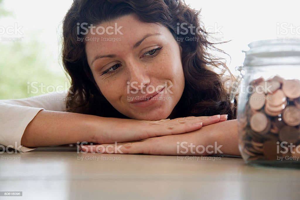 Woman looking at a jar of pennies stock photo