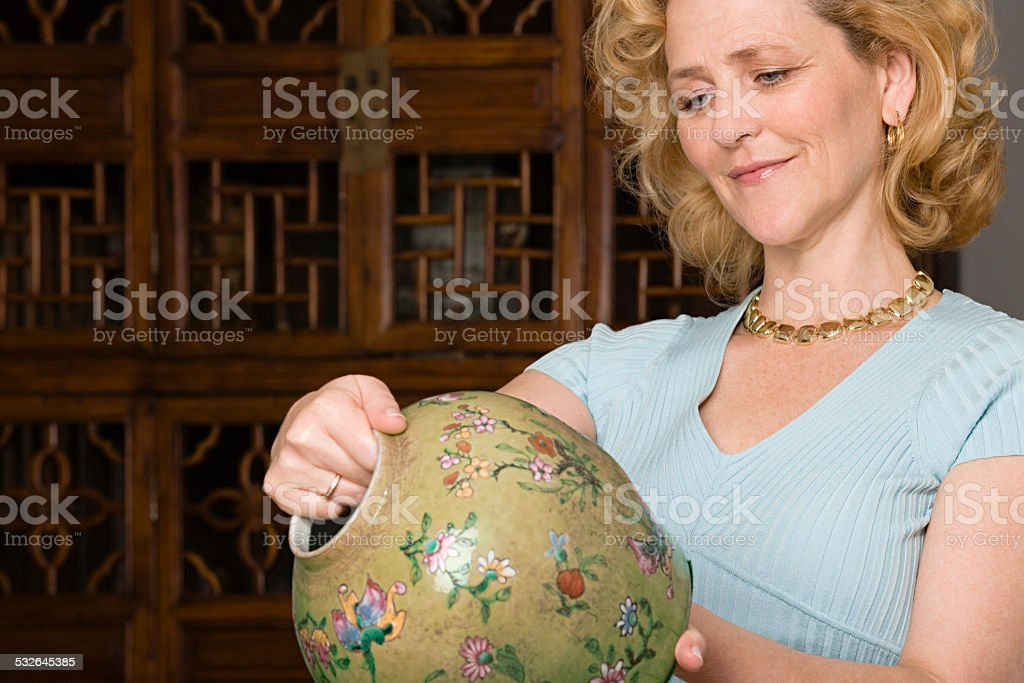 Woman looking at a vase stock photo