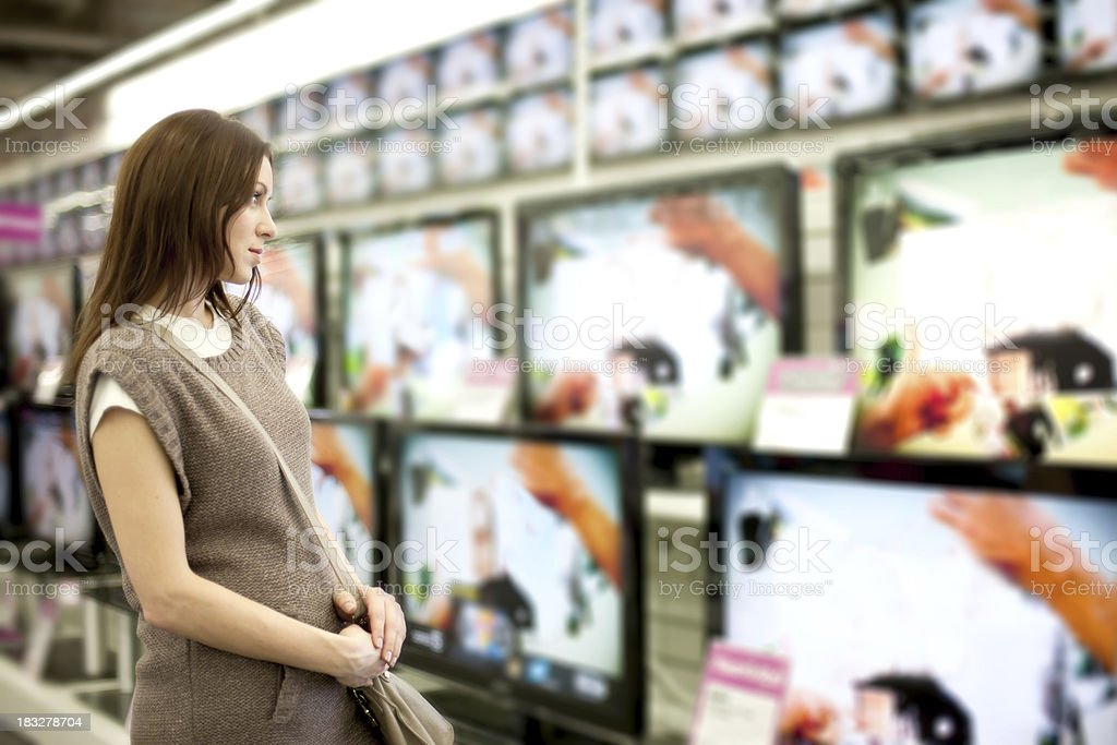 A woman looking at a wall of televisions for purchase stock photo