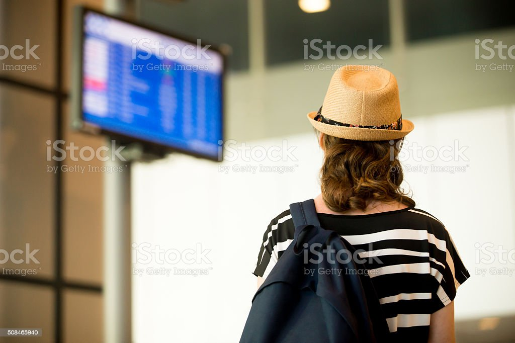 Woman looking at airport flight information board stock photo
