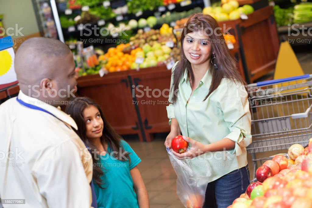 Woman looking at apples with daughter and supermarket produce worker royalty-free stock photo