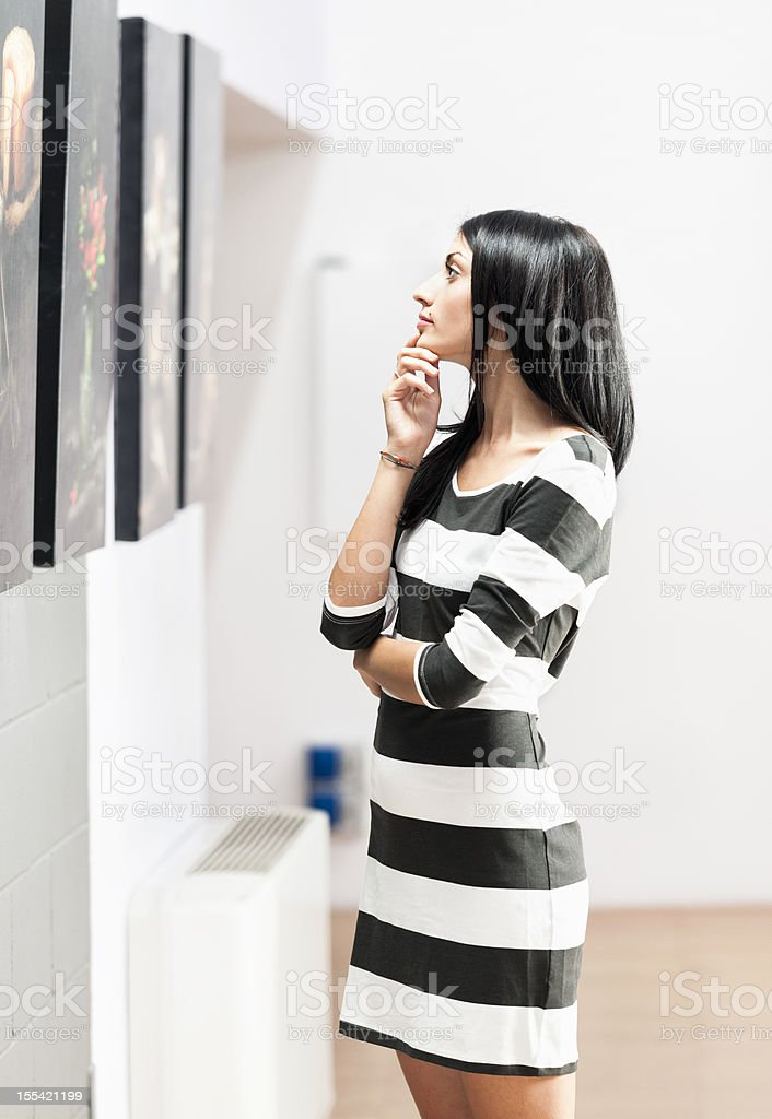 Woman Looking at Art Gallery Pictures stock photo