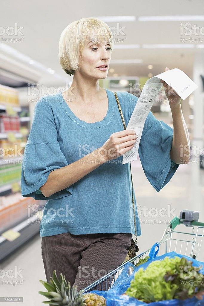 Woman looking at bill in grocery store royalty-free stock photo