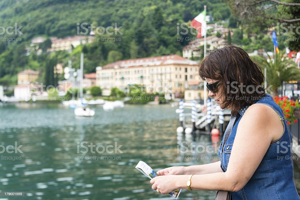 Woman looking at brochure on the lake royalty-free stock photo