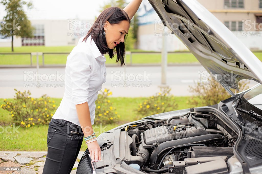 Woman looking at broken cars motor stock photo