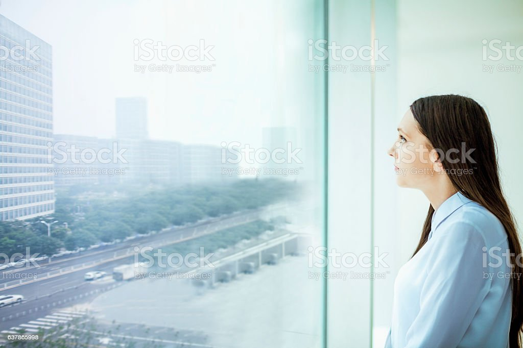 Woman looking at cityscape from window in office stock photo