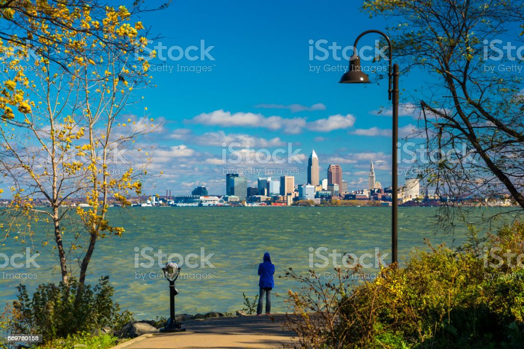 Woman Looking At Cleveland Skyline From Park stock photo