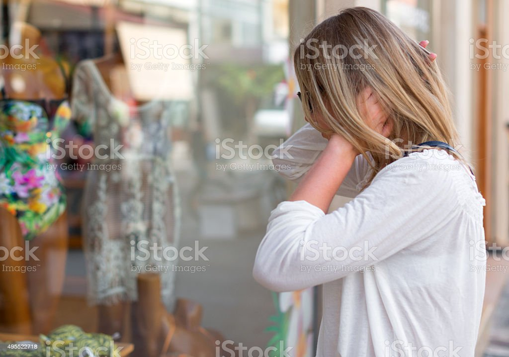 Woman looking at display window in fashion store. stock photo