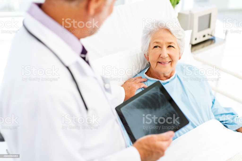 Woman Looking At Doctor With X-Ray On Digital Tablet stock photo