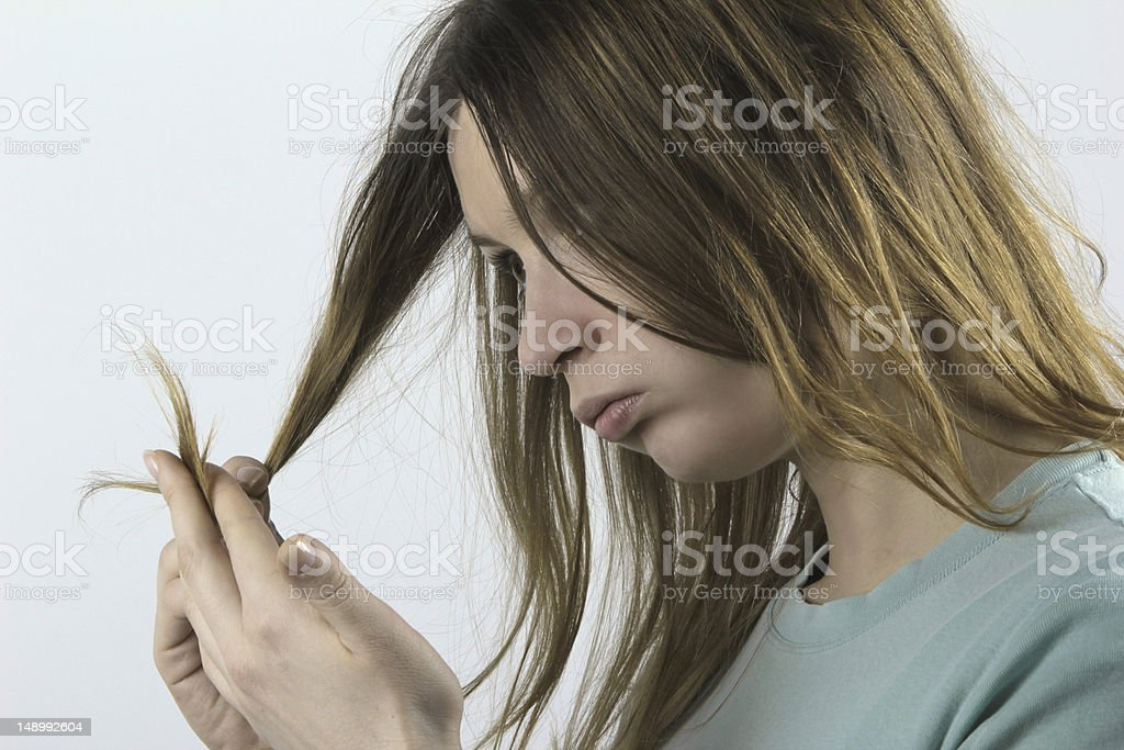 Woman looking at ends of damaged hair stock photo
