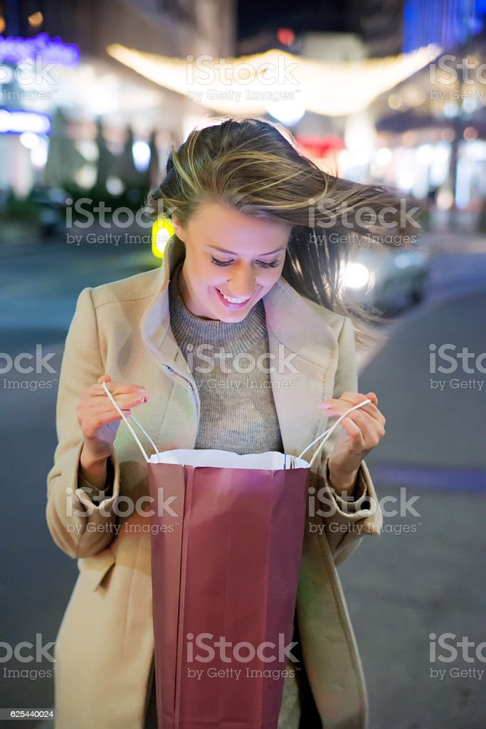 woman looking at gift bag on the street at night stock photo