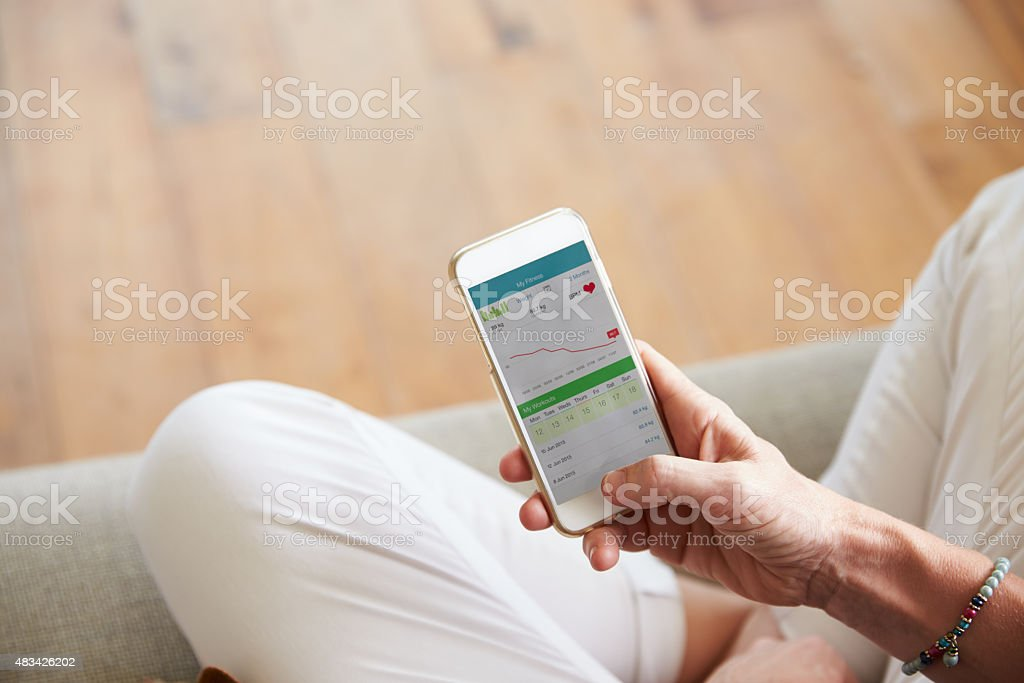 Woman Looking At Health Monitoring App On Smartphone stock photo