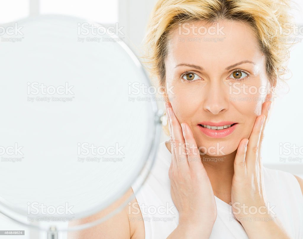 A woman looking at her face in the mirror stock photo